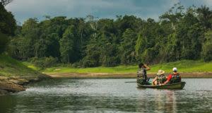 people sitting in canoe enjoying views of Amazon