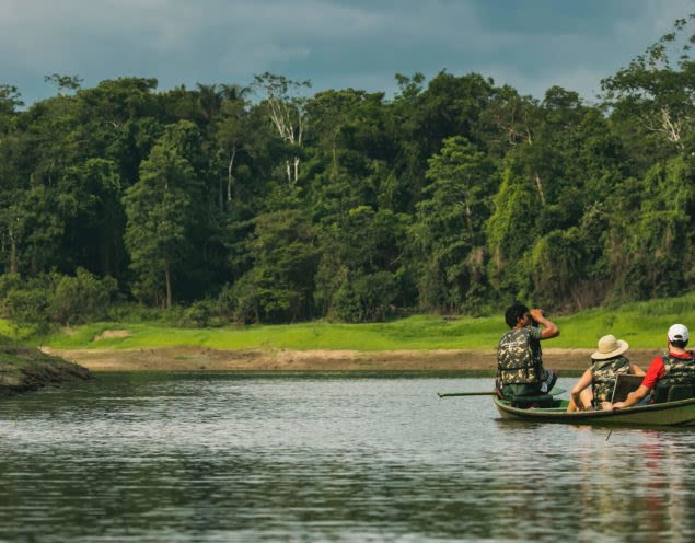 people sitting in canoe enjoying views of Amazon