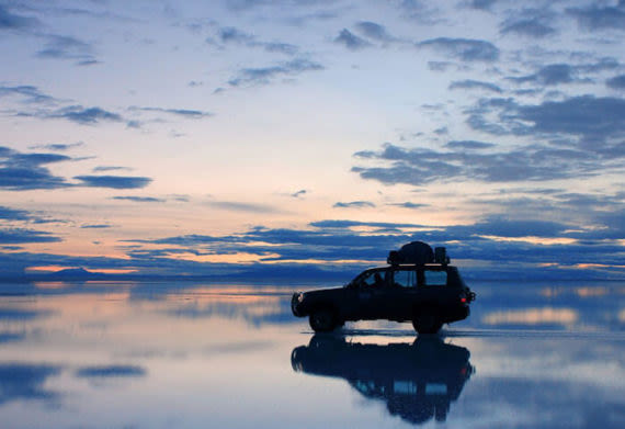 car driving through the mirrored salt flats of uyuni