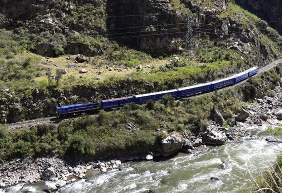 train running along the river to machu picchu