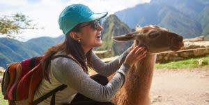 woman at Machu Picchu petting a llama