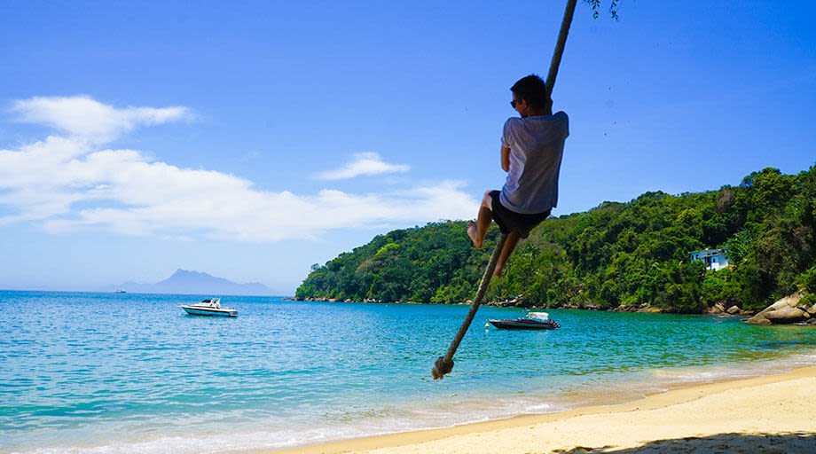 Man on tight rope in Ilha Grande Brazil