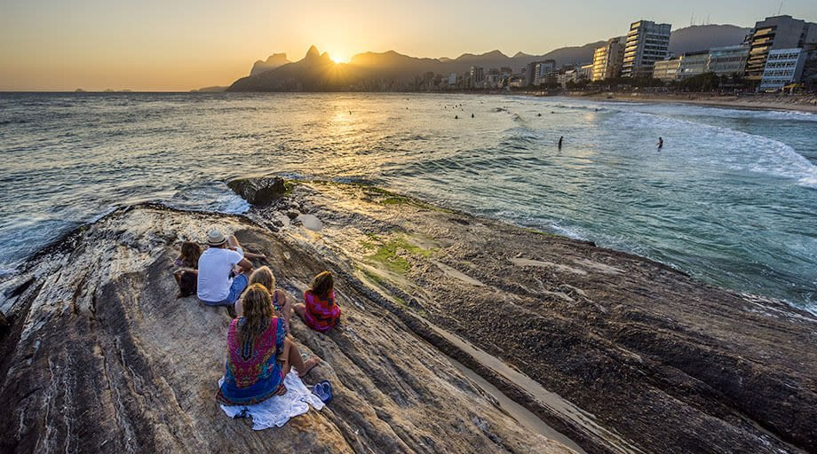 people sitting on rock at the beach near copacabana in rio de janeiro