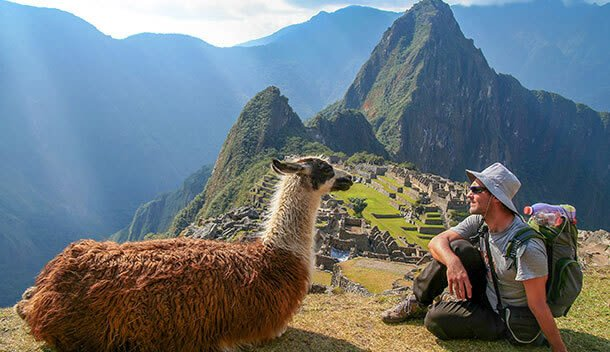 tourist sitting at machu picchu ruins