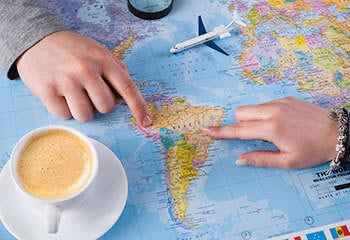 Couple planning a trip on a South America map